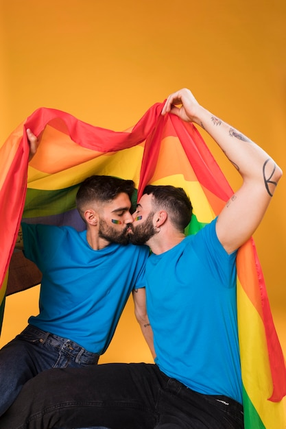 Young men kissing under lgbt flag Free Photo