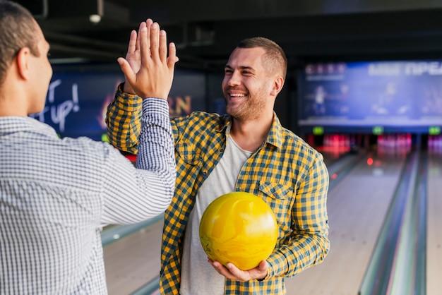 Giovani uomini in piedi in un club di bowling Foto Gratuite