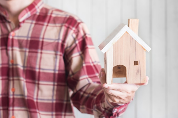 Young men wear red gingham shirt holding miniature house model, property investment concept, copyspace Premium Photo