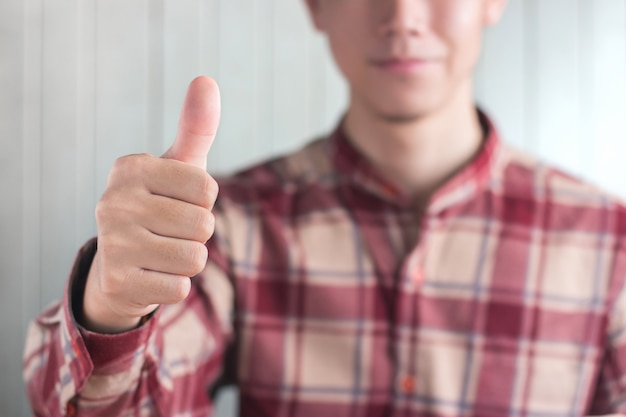 Young men wear red scott pattern shirt show finger thumb up on white wood Premium Photo
