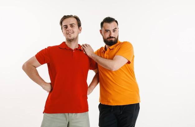 Молодые люди носили цвета флага лгбт, изолированные на белой стене. кавказские модели-мужчины в ярких рубашках. выглядите счастливым, улыбающимся и обнимающимся. концепция гордости, прав человека и выбора лгбт. Бесплатные Фотографии