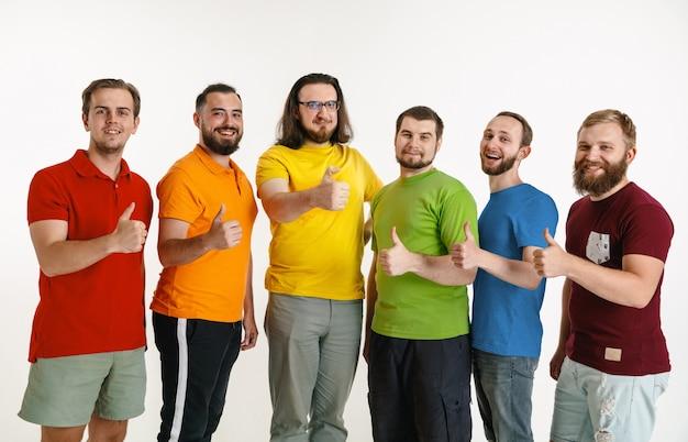 Молодые люди носили цвета флага лгбт, изолированные на белой стене. кавказские мужчины-модели в рубашках красного, оранжевого, желтого, зеленого, синего и фиолетового цветов. концепция гордости, прав человека и выбора лгбт. Бесплатные Фотографии