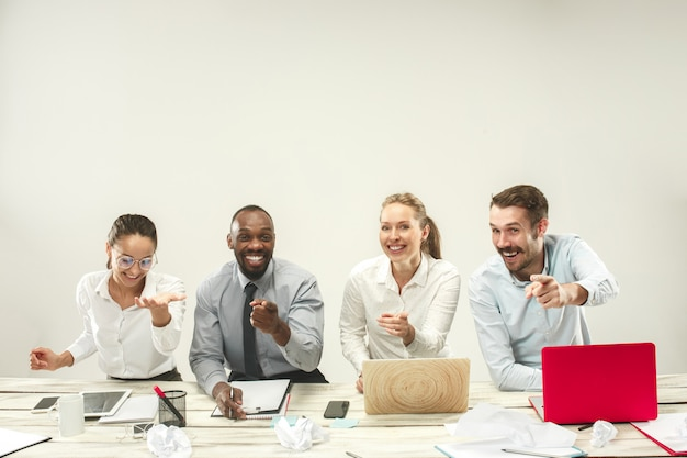 Young men and women sitting at office and working on laptops. emotions concept Free Photo