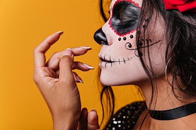 Giovane ragazza messicana con rose tra i capelli e arte a forma di teschio sul viso posa carina con gli occhi chiusi Foto Gratuite