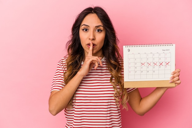 Young mexican woman holding a calendar isolated on pink keeping a secret or asking for silence. Premium Photo