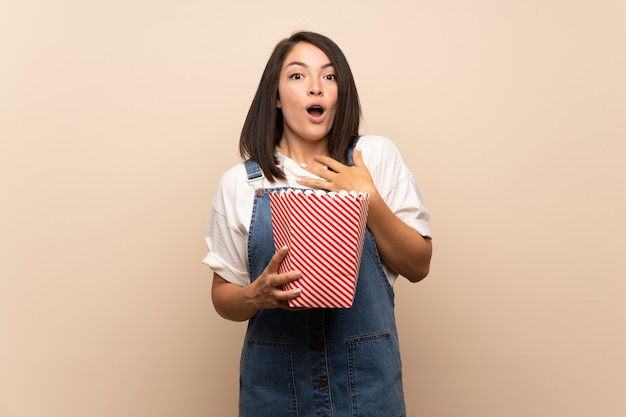 Young mexican woman over isolated background holding a bowl of popcorns Premium Photo
