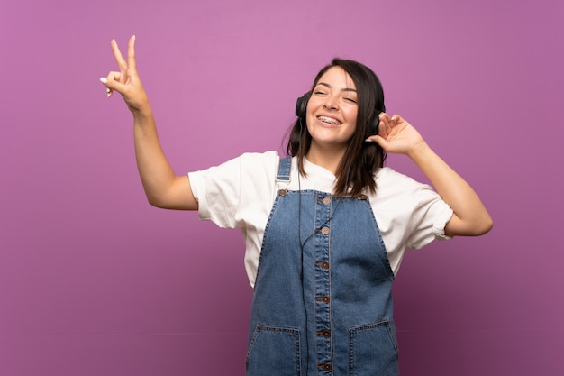 Young mexican woman over isolated background listening to