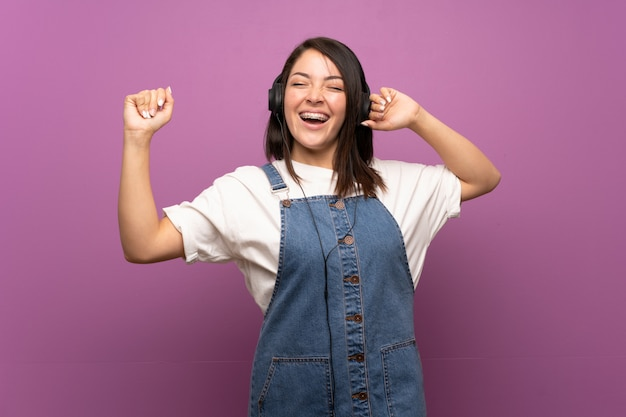 Young mexican woman over isolated  listening to music with headphones Premium Photo