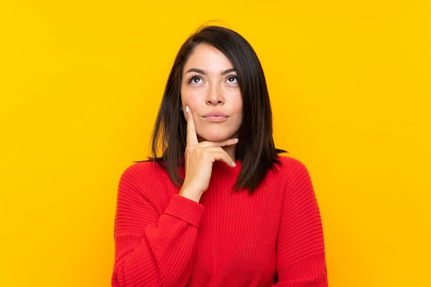 Young mexican woman with red sweater over yellow wall thinking an idea Premium Photo