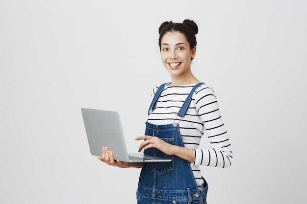 Giovane ragazza millenaria utilizzando laptop, studentessa saggio di scrittura sul computer Foto Gratuite