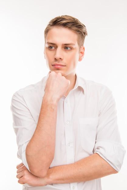 Молодой предприниматель, трогающий его подбородок Premium Фотографии