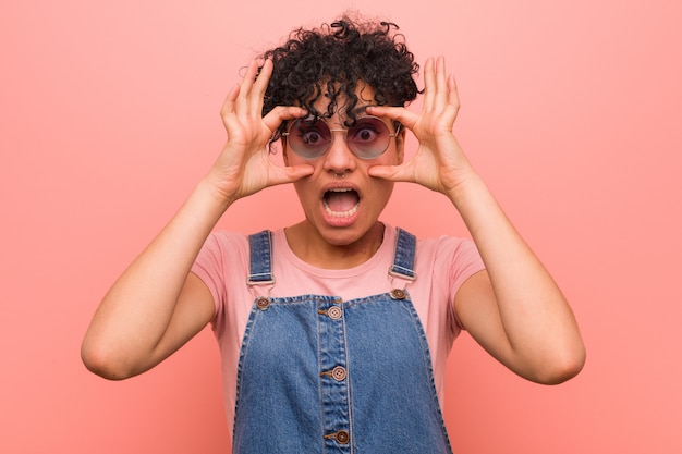 Young mixed african american teenager woman keeping eyes opened to find a success opportunity. Premium Photo