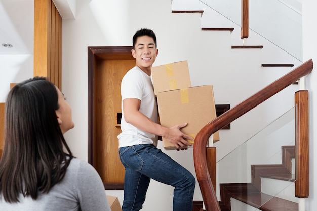 Young mixed-race couple bringing cardboard boxes to their new apartment Free Photo