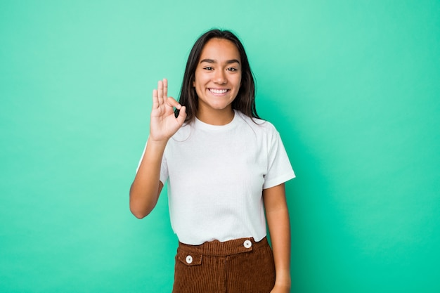 Young mixed race indian woman isolated cheerful and confident showing ok gesture. Premium Photo