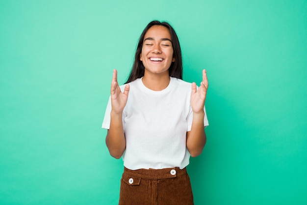 Young mixed race indian woman isolated joyful laughing a lot. happiness concept. Premium Photo