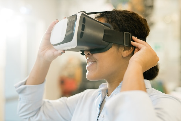 Young mixed-race woman taking on vr headset on head to watch presentation of new assortment and choose product Premium Photo
