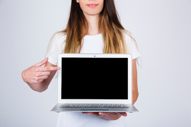 Young model holding and pointing laptop Free Photo