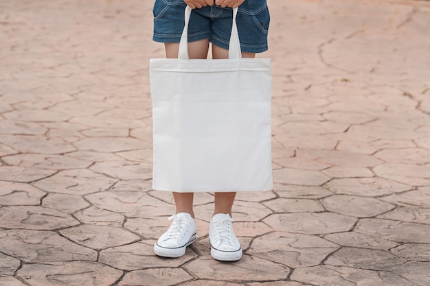 Young model holding white tote bag for mockup blank template Premium Photo