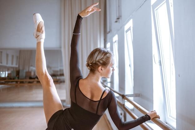 Il giovane ballerino moderno in posa contro il muro della stanza Foto Gratuite