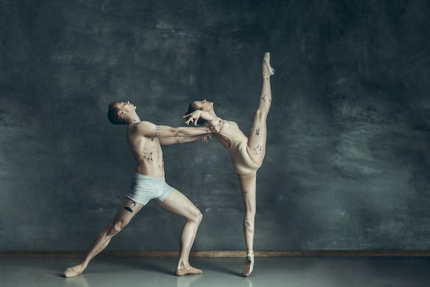 Young modern ballet dancers posing on gray Free Photo