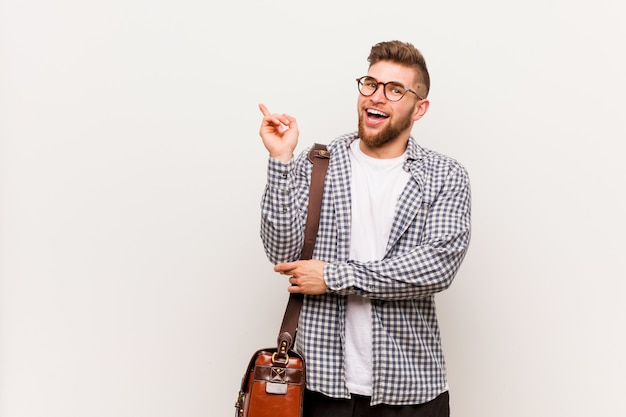 Young modern business man smiling cheerfully pointing with forefinger away. Premium Photo