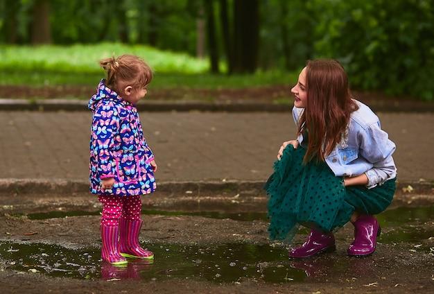 若いお母さんと小さな娘が公園のプールでガウンで遊んで楽しい 無料写真
