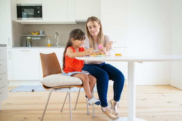 イースターエッグを押し、笑みを浮かべて、キッチンで娘を見せている若いお母さん。 無料写真
