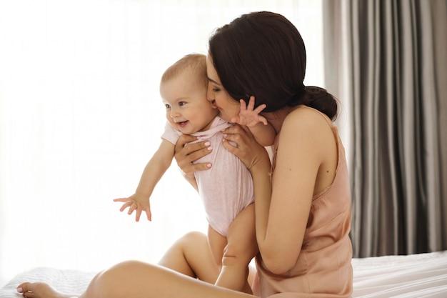 Молодая мама в пижамы, улыбаясь, обнимая, целуя ее ребенка, сидя в кровати над окном. закрытые глаза. Бесплатные Фотографии