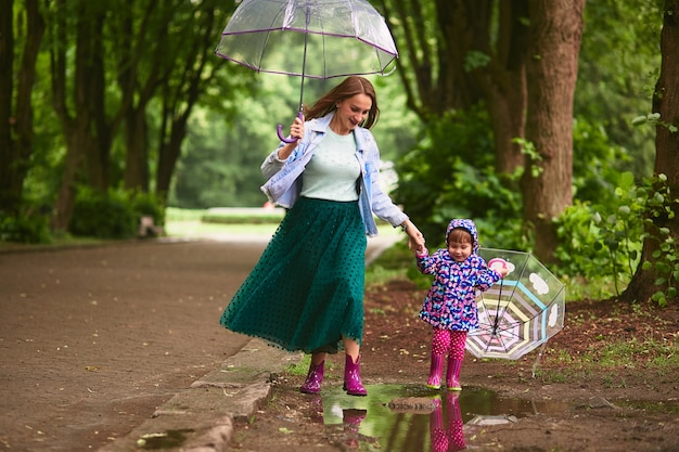 Young mom and little daugther have fun walking with umbrellas on the pools after the rain Free Photo
