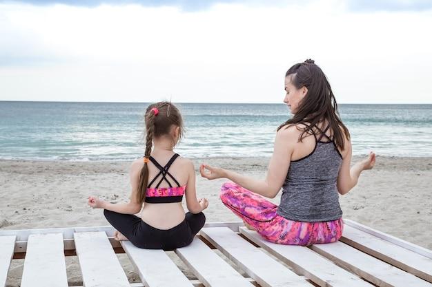 若い母と娘は海のビーチでヨガと瞑想を練習します。 無料写真