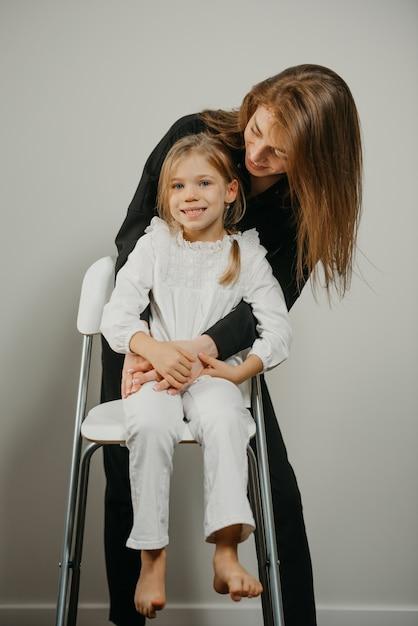 젊은 어머니와 키가 큰 의자에 그녀의 딸 프리미엄 사진