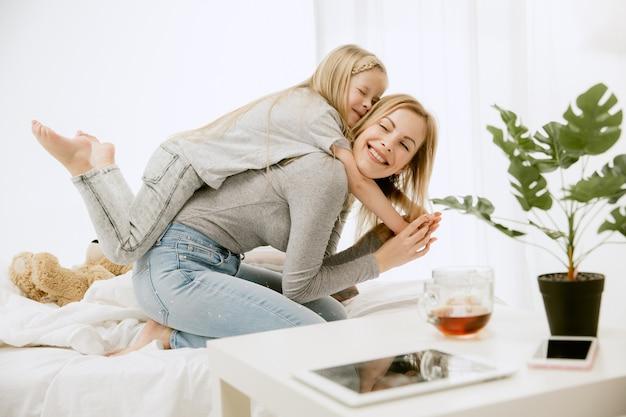 Молодая мать и ее маленькая дочь дома в солнечное утро. мягкие пастельные тона. счастливое семейное время на выходных. концепция дня матери. понятия семьи, любви, образа жизни, материнства и нежных моментов. Бесплатные Фотографии