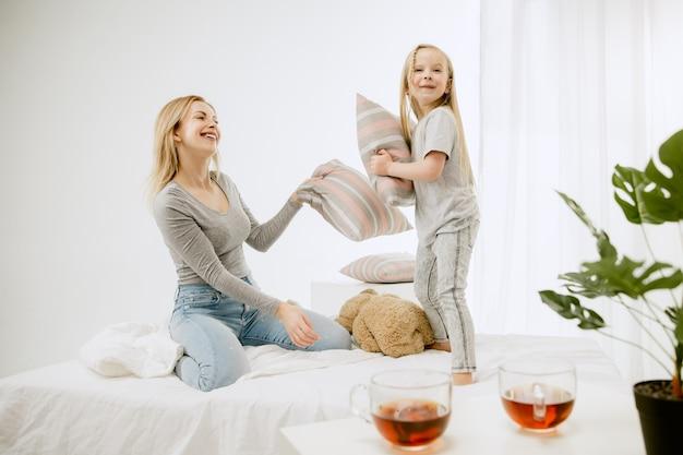 Молодая мать и ее маленькая дочь дома в солнечное утро. мягкие пастельные тона. счастливое семейное время на выходных. Бесплатные Фотографии