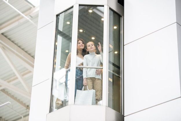 Young mother and daughter discussing something while moving upwards in elevator during black friday shopping in the mall Premium Photo