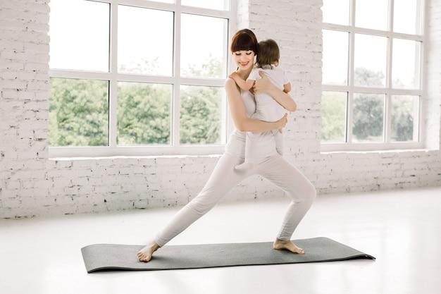 젊은 어머니는 그녀의 아기와 함께 신체 요가 운동을 않습니다. 체조와 운동을하는 아기와 엄마 프리미엄 사진