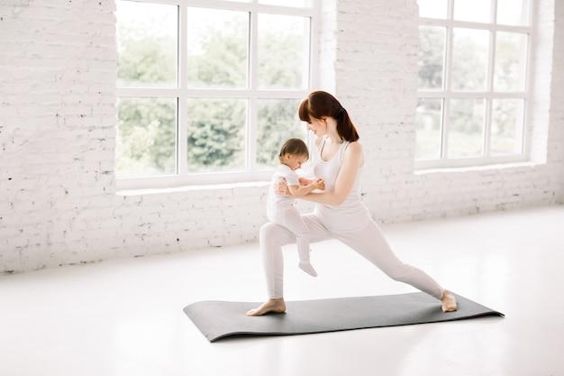 큰 빛 체육관 홀에서 그녀의 작은 아기와 함께 요가, 폐를하고 젊은 어머니 프리미엄 사진