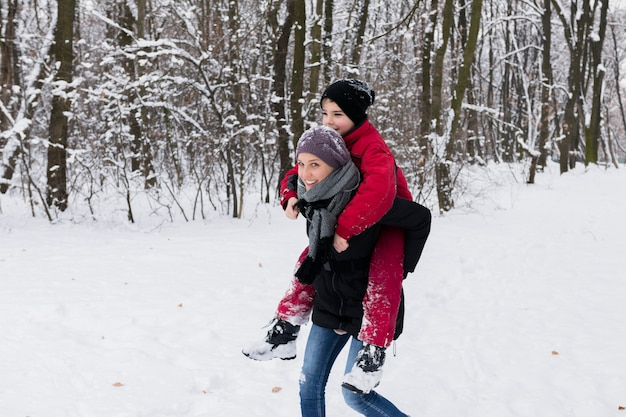 Young mother giving piggy back at forest on a winter day Free Photo