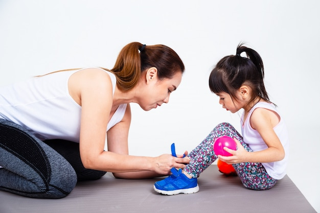 Young mother help cute daughter wearing shoes Free Photo