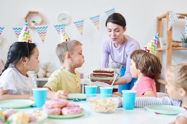 若い母親が小さな女の子がホームパーティー中にバースデーケーキにろうそくを吹くのを助けたテーブルの周り Premium写真