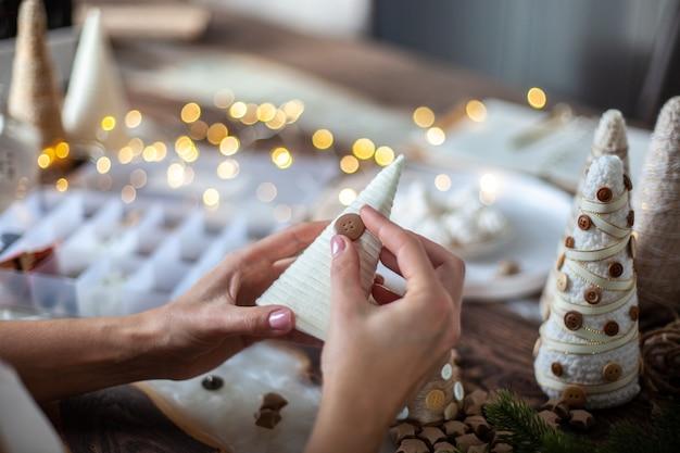 若い母親は、フォームコーンを紐や毛糸で包み、テーブルの装飾用にさまざまなサイズのクリスマスツリーを作るために娘を助けています。ホリデーシーズンとパーティーの準備のコンセプト。 Premium写真