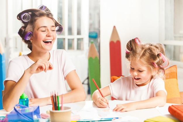 The young mother and her little daughter drawing with pencils at home Free Photo