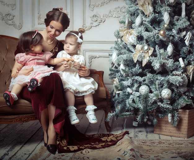Young mother and her two little daughters near christmas tree Premium Photo