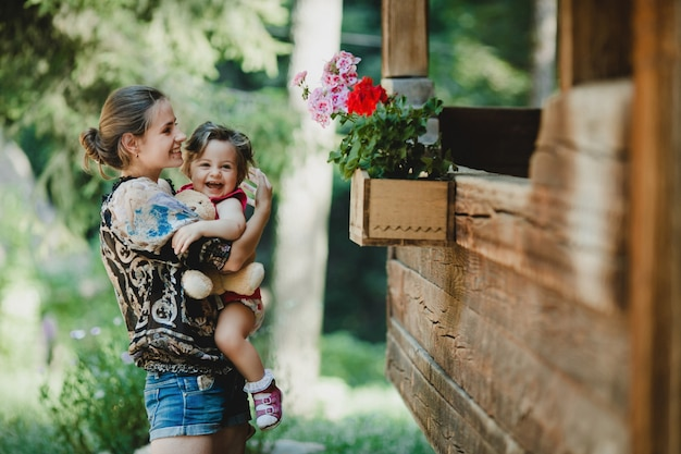 Young mother holds joyful little child standing with her before old wooden house Free Photo