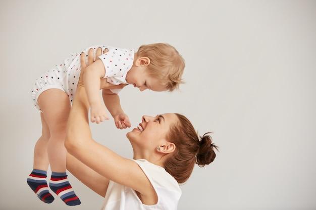 침대에 그녀의 작은 아기와 함께 노는 젊은 어머니 무료 사진