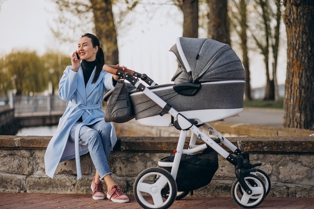 Young mother sitting with baby carriage in park Free Photo