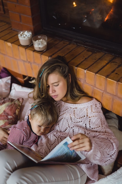 A young mother and son are reading a fairy tale book near the fireplace. Free Photo