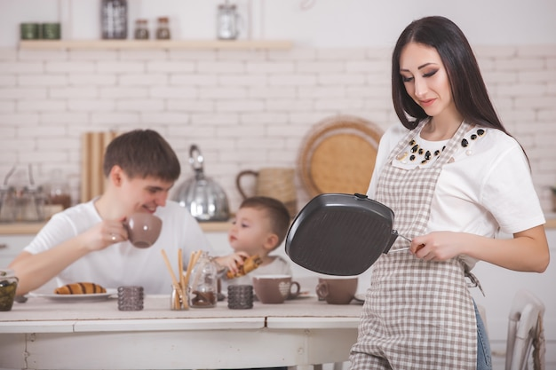 Young mother standing infront of her family on the kitchen. happy family having dinner or breakfast. woman making dinner for her husband and little baby. Premium Photo
