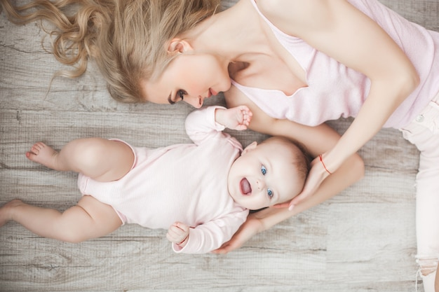 Premium Photo | Young mother taking care of her little baby girl. beautiful  mom and her daughter indoors in the bedroom. loving family. attractive mum  holding her child.