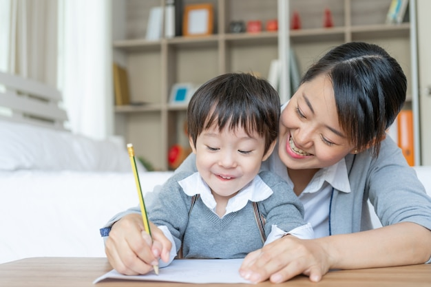 Young mother teaching her son write on paper with love Free Photo
