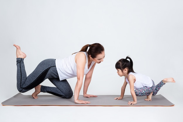 Young mother training lovely daughter with yoga Free Photo